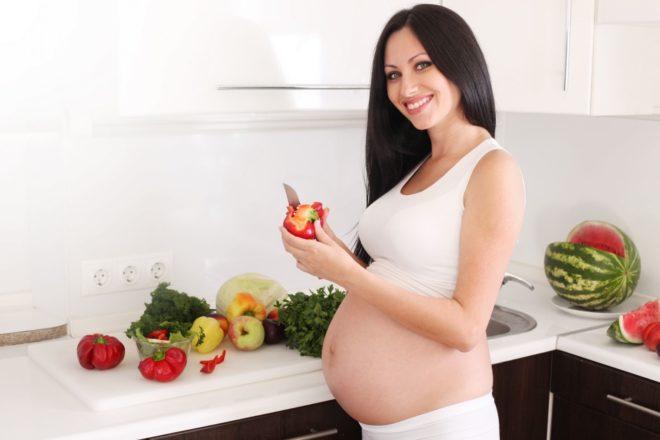 Беременная девушка на кухне готовит